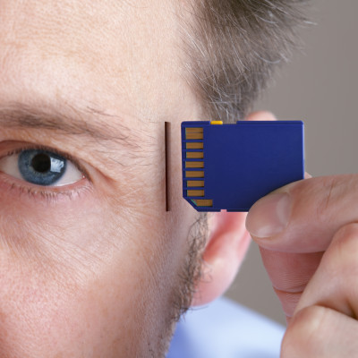 Inserting SD memory card into slot in human head concept for memory upgrade, forgetfulness or computing